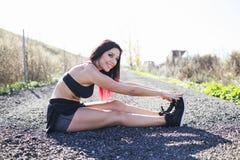 Giovane corridore della donna di forma fisica che allunga le gambe Immagine Stock Libera da Diritti