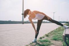 Giovane corridore della donna di forma fisica che allunga le gambe prima del funzionamento Fotografia Stock