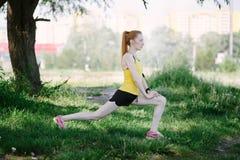 Giovane corridore della donna di forma fisica che allunga le gambe prima del funzionamento Immagini Stock Libere da Diritti