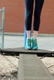 Giovane corridore della donna di forma fisica che allunga le gambe prima del funzionamento Immagini Stock