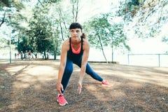 Giovane corridore della donna di forma fisica che allunga le gambe prima del funzionamento Fotografia Stock Libera da Diritti