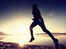 Giovane corridore esile sulla spiaggia, corridore tropicale dell'uomo di forma fisica della traccia Sportivo allegro fatto funzio Immagine Stock