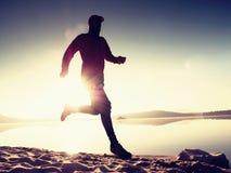 Giovane corridore esile sulla spiaggia, corridore tropicale dell'uomo di forma fisica della traccia Sportivo allegro fatto funzio Fotografie Stock