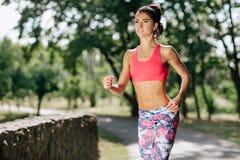 Giovane corridore femminile che pareggia durante l'allenamento all'aperto in un parco Bella ragazza di misura Perdita di peso Sti Immagini Stock Libere da Diritti