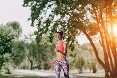 Giovane corridore femminile che pareggia durante l'allenamento all'aperto in un parco Bella ragazza di misura Perdita di peso Sti Immagine Stock