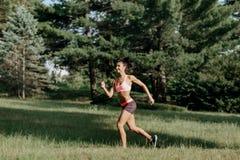 Giovane corridore femminile che pareggia durante l'allenamento all'aperto in un parco Bella ragazza di misura Perdita di peso Sti Fotografia Stock