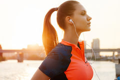 Giovane corridore femminile che pareggia sopra il tramonto, lato del fiume, città urbana co immagine stock libera da diritti