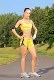 Giovane corridore femminile che posa su una pista corrente in parco Fotografia Stock