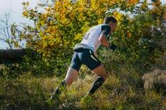 Giovane corridore maschio che corre in salita, intorno al paesaggio di autunno Immagine Stock Libera da Diritti