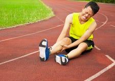 Giovane corridore maschio che soffre dal crampo di gamba sulla pista Immagini Stock Libere da Diritti