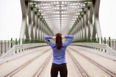Giovane corridore nella città che allunga sul ponte d'acciaio verde Fotografia Stock Libera da Diritti