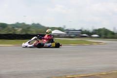 Giovane corridore professionista con la concorrenza al suo da go-kart in una concorrenza Fotografie Stock Libere da Diritti