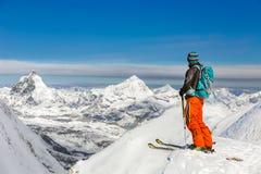 Giovane corsa con gli sci atletica dell'uomo un giorno soleggiato con la bella vista di Fotografia Stock