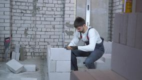 Giovane costruttore che pone blocco in calcestruzzo aerato e che lo controlla con la livella a bolla archivi video