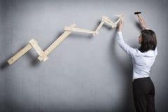 Giovane costruzione della donna di affari che indica sul grafico Fotografia Stock