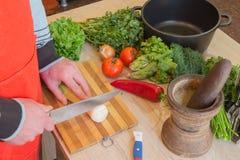 Giovane cottura maschio nella cucina Alimento sano Immagine potata delle verdure di taglio del giovane per alimento Fotografia Stock