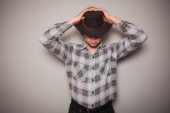 Giovane cowboy in camicia di plaid contro una parete verde Fotografie Stock