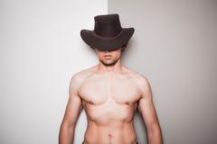 Giovane cowboy senza camicia contro fondo verde e bianco Fotografia Stock