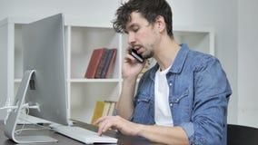 Giovane creativo che parla sul telefono e che per mezzo del desktop stock footage