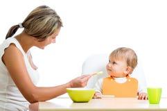 Giovane cucchiaio della mamma che alimenta la sua neonata sveglia Fotografie Stock Libere da Diritti