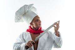 Giovane cuoco bello su un fondo bianco in un grande cappuccio Fotografia Stock