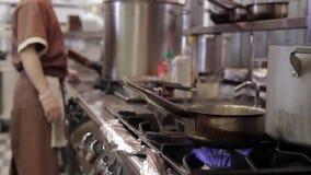 Giovane cuoco unico che prepara alimento accanto al fornello in grande ristorante moderno archivi video