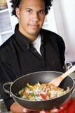 Giovane cuoco unico con il wok Immagini Stock Libere da Diritti