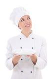 Giovane cuoco unico di sogno della donna nell'isolato vuoto del piatto della tenuta uniforme Immagine Stock