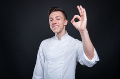 Giovane cuoco unico felice che mostra gesto e sorridere giusti Fotografie Stock