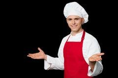 Giovane cuoco unico maschio che accoglie favorevolmente i suoi ospiti Immagini Stock Libere da Diritti