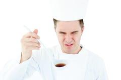 Giovane cuoco unico maschio che assagia una minestra con il fronte storto immagini stock