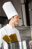 Giovane cuoco unico maschio Standing In Kitchen Immagini Stock