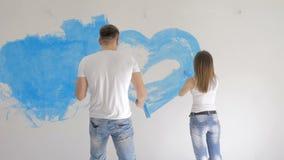 Giovane cuore della pittura delle coppie sulla parete con pittura blu stock footage