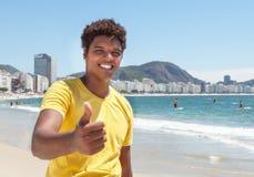 Giovane da Rio in una camicia gialla che mostra pollice a Copacabana Fotografia Stock Libera da Diritti