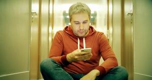 Giovane dai capelli grigio in abbigliamento casual facendo uso del suo smartphone nel corridoio dell'hotel video d archivio