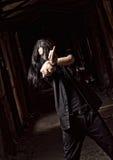 Giovane dai capelli lunghi che fa gesto offensivo (dito medio) Fotografia Stock