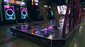 Giovane dancing asiatico della ragazza e giocare il gioco di rivoluzione di ballo su Arcade Machine Pad nel centro commerciale di video d archivio