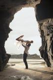 Giovane dancing romantico delle coppie attraverso l'arco della roccia alla spiaggia Fotografia Stock