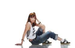 Giovane danzatore femminile confuso che si siede sul pavimento lucido Immagine Stock