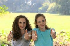 Giovane dare motivato delle sorelle pollici su Immagine Stock Libera da Diritti