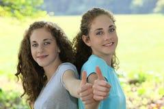 Giovane dare sorridente delle sorelle pollici su Immagini Stock Libere da Diritti
