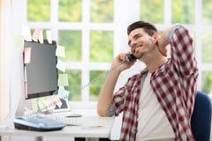 Giovane davanti al computer che parla sul telefono Immagini Stock