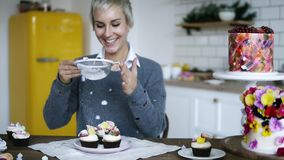 Giovane decorazione femminile saporita, del confettiere bigné decorati immaginazione La donna con lo zucchero a velo colorato gri archivi video