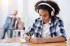 Giovane dedicato che ascolta la musica mentre studiando Fotografia Stock