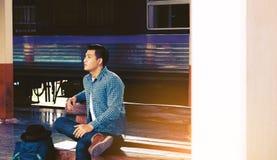 Giovane dei pantaloni a vita bassa asiatici che si siede alla stazione ferroviaria con attendere t Fotografia Stock Libera da Diritti