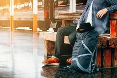 Giovane dei pantaloni a vita bassa asiatici che si siede alla stazione ferroviaria con attendere t Immagini Stock