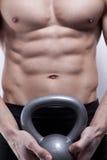 Giovane del muscolo con i kettlebells Fotografia Stock