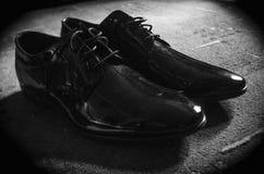 Giovane del primo piano che lega le scarpe eleganti all'interno, scarpa, maschio, cuoio, fotografia stock