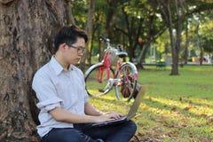 Giovane del ritratto che si rilassa con un computer portatile per la rete sociale nel parco di estate Immagine Stock