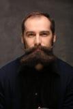 Giovane del ritratto con i pantaloni a vita bassa lunghi dei baffi e della barba immagini stock libere da diritti